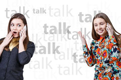 Two young girls talking by cell phones Stock Photography