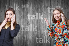 Two young girls talking by cell phones Royalty Free Stock Images