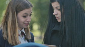 Two young girls talking and use the tablet. Close-up. Two young girls looking in the tablet and discuss some information. Smiling girls have a conversation. The stock video footage