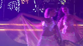 Two young girls in theatrical costumes dance. Two young girls wearing theatrical costumes with silver wings dancing at the wedding party in red light stock video