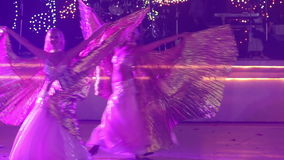 Two young girls in theatrical costumes dance. Two young girls wearing theatrical costumes with silver wings dancing at the wedding party in red light stock footage