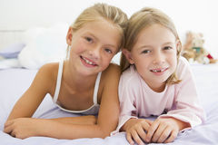 Two Young Girls In Their Pajamas Lying On A Bed Royalty Free Stock Photography