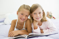 Two Young Girls In Their Pajamas, Reading A Book Stock Images
