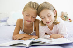 Two Young Girls In Their Pajamas, Reading A Book Stock Image