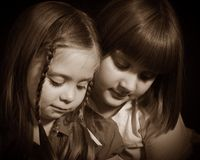 Two young girls thoughtfully looking down Stock Photos