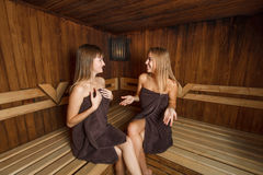 Two young girls in towels in sauna. Royalty Free Stock Image
