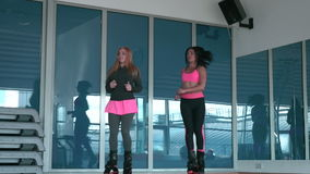 Two young girls training in kangoo shoes in the gym stock video footage