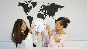 Two young girls twins with clock. On the background of the world map stock footage