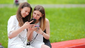 Two young girls using smart phone outdoors. Two women sitting in park with coffee and using smartphone stock footage