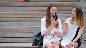 Two young girls using smart phone outdoors. Two women sitting in park with coffee and using smartphone stock video footage