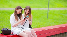Two young girls using smart phones outdoors. Two women sitting in park and sending message by smartphone stock video footage