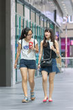 Two young girls walk in a shopping mall, Beijing, China Stock Image