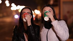 Two young girls walk through the streets of an unfamiliar city on an autumn evening and drink coffee stock footage