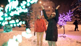 Two young girls walk in the winter through the decorated streets of the city. New year, holiday, snow.  stock footage