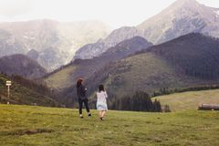 Two young girls walking on a green meadow among the mountains royalty free stock photos