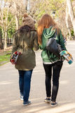 Two young girls walking skates in hand Royalty Free Stock Photos