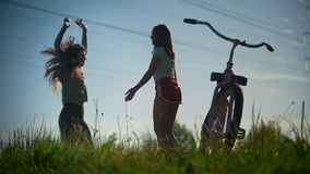 Two young girls warm up, jump before a bike ride, sunny day. Two young famale warm up, jump before a bike ride,sunny summer day, telephoto shot stock footage