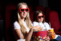 Two young girls watching in cinema Royalty Free Stock Images