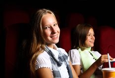 Two young girls watching in cinema Stock Photo