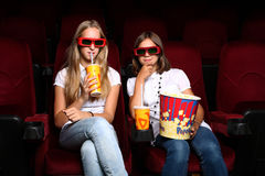 Two young girls watching in cinema Stock Photos