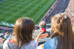 Two young girls watching a football game Royalty Free Stock Photography