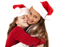 Two young girls wearing santa hats hugging Stock Images