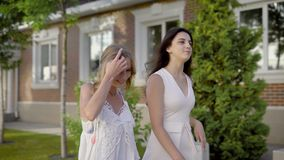 Two young girls in white summer dresses walking down street and looking away dreamily. Two young stylish women strolling together along street in summertime stock video footage