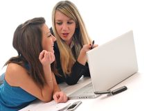 Two young girls work on laptop isolated Royalty Free Stock Photos