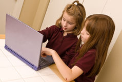 Young girls working on a laptop computer. Two young girls working on a laptop computer. One young watches as the other girl points out something on the keyboard Stock Photography