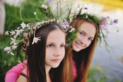 Two young girls in wreaths of wild flowers Stock Photography