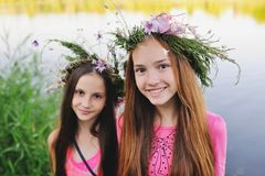 Two young girls in wreaths of wild flowers Royalty Free Stock Photography