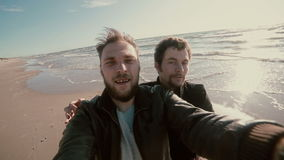 Two young goofy guys with beards are standing on a sandy beach trying to take a selfie. Two young goofy guys with beards are standing on a sun-lit sandy beach stock video
