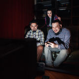 Two young guy play video game on couch, girl watch. Two young guys with joysticks play video game on couch at home, in dark room. Concentrated girl watch Stock Photo