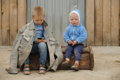 Two young guy plays with a phone. And a prize for races on a rural farmstead in a hot summer royalty free stock photography