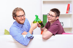 Two young guys with beer on the sofa. At home royalty free stock image
