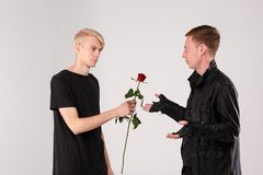 A guy with blonde hair gives a brunette guy a rose to a who is indignant. Two young guys are brunette and blond. A guy with blonde hair gives a brunette guy a Stock Image
