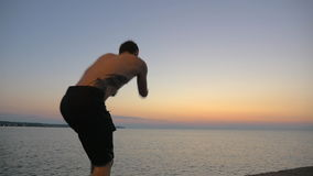 Two young guys doing tricks jumping from pier. Slow motion steadicam clip of two young men doing acrobatic tricks while jumping from the pier into sea at sunset stock video
