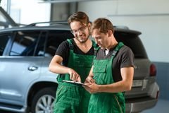 Two young guys in green overalls work at a car service royalty free stock photo