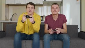 Two young guys playing a video game at home on the couch against the background of the kitchen