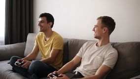 Two young guys playing video games at home, holding joysticks and sitting on the grey sofa in loft interior room.Smiling