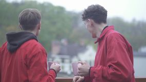 Two young guys in red jackets cheers with coffe cups and smile Friends spend time outdoors together Male friendship. Two men in red jackets cheers with coffee stock video