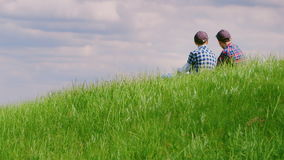 Two young guys sit on top of a green hill, communicate and dream. Against the background of a beautiful blue sky with. Two teenage boys in caps sit on a green stock video footage