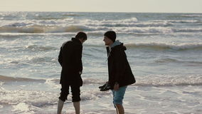 Two young guys are soaking their feet in the waves of the sea smiling and talking to each other. Two young guys are soaking their feet in the waves of the sea stock video