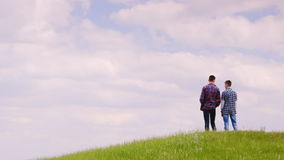 Two young guys stand on top of a green mountain. They look forward to the horizon. Against the blue sky in a picturesque stock video footage