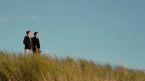 Two young guys are standing in tall grass on a windy day looking in the same direction. Two young guys in black outerwear are standing in tall grass on a windy stock footage
