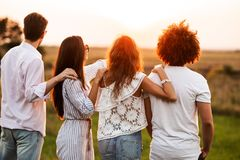 Two young guys and two girls dressed in a stylish clothes are standing in the field and looking in front of them on a. Sunny day royalty free stock images