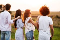Two young guys and two girls dressed in a stylish clothes are standing in the field and looking in front of them on a. Sunny day royalty free stock photo