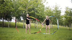 Two young gymnasts with tape performs exercises in the Park. stock video