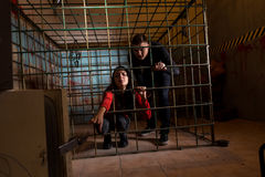 Two young Halloween victims imprisoned in a metal cage, girl pul Stock Photos