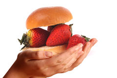 Two young hands offering strawberry on a bun Royalty Free Stock Images